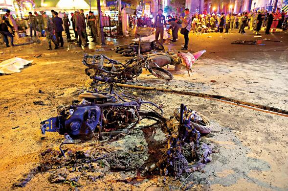 泰国曼谷四面佛地区17日发生爆炸后,现场可见烧焦的电单车残骸,及