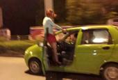 馬路上的一幕:短裙女子手抓車頂 懸在車外