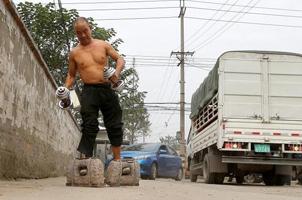 民间健身达人:成都大叔挂百斤石锁散步