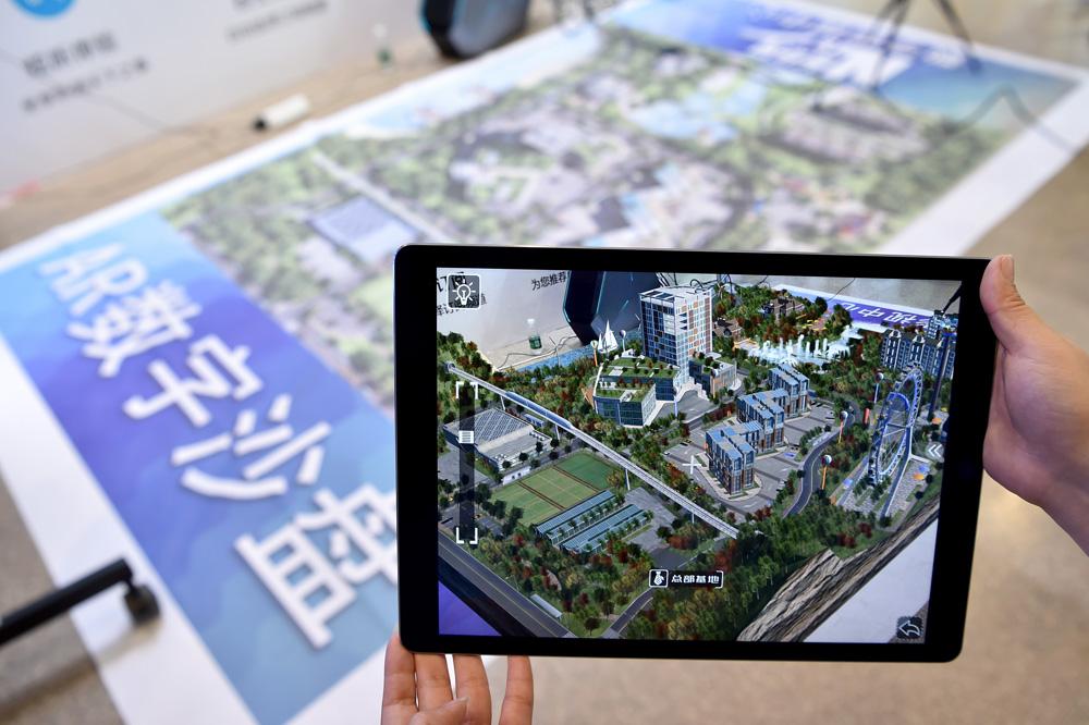 图为新华网展台的工作人员向记者展示ar数字沙盘产品新华社