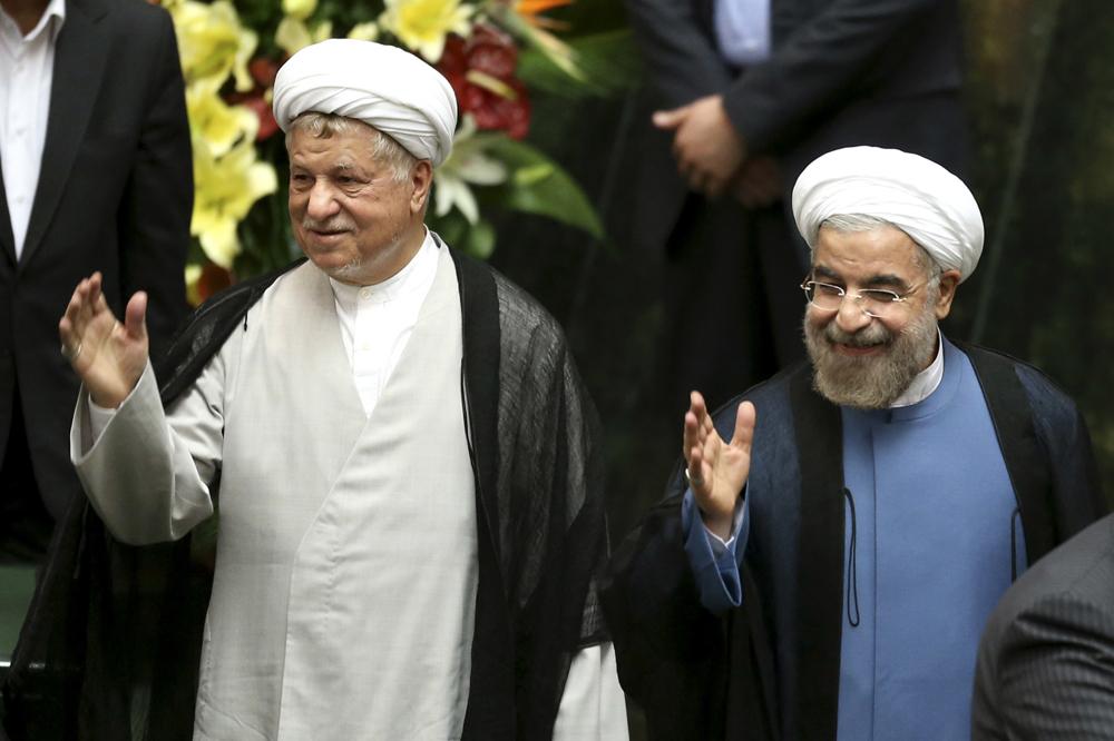 贾尼/图:伊朗前总统拉夫桑贾尼(左)和伊朗现任总统鲁哈尼/美联社