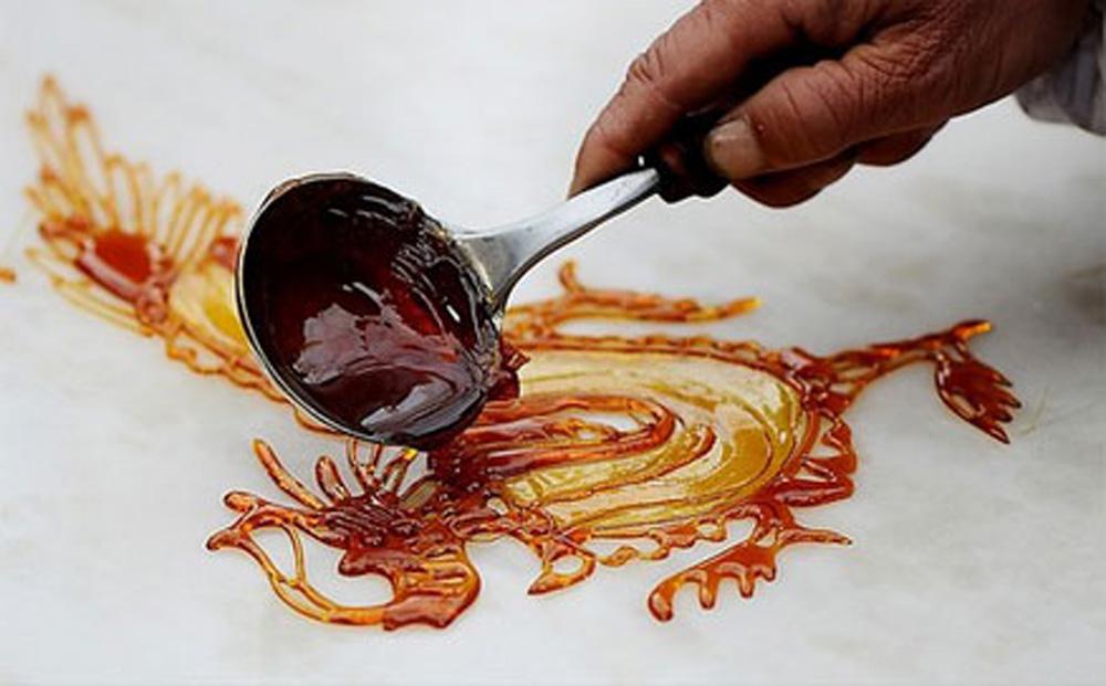 印象中的糖画由一根竹签黏起,孩童们转动十二生肖的转盘来挑画,无