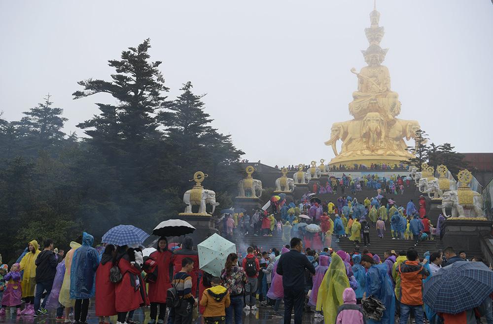 图:3日,在四川峨眉山景区,大批游客冒雨游览金顶中新社