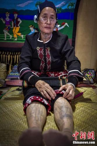 75岁的黎族阿婆符金花展示腿部文身。骆云飞 摄