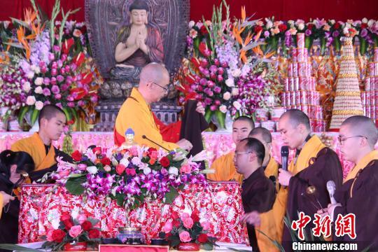 中国佛教协会会长、莆田广化寺方丈学诚大和尚为优婆塞、优婆夷的代表授搭缦衣。 龙天 摄